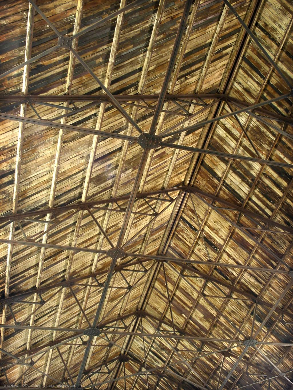 Underside of an industrial warehouse ceiling, with steel trusses supporting a wood slat roof