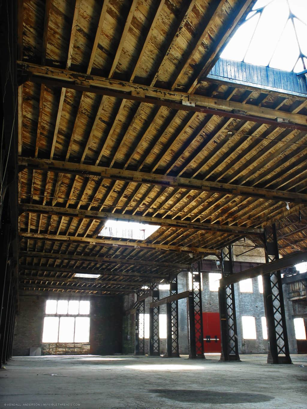Wood joists holding up ceiling of industrial warehouse, with skylights