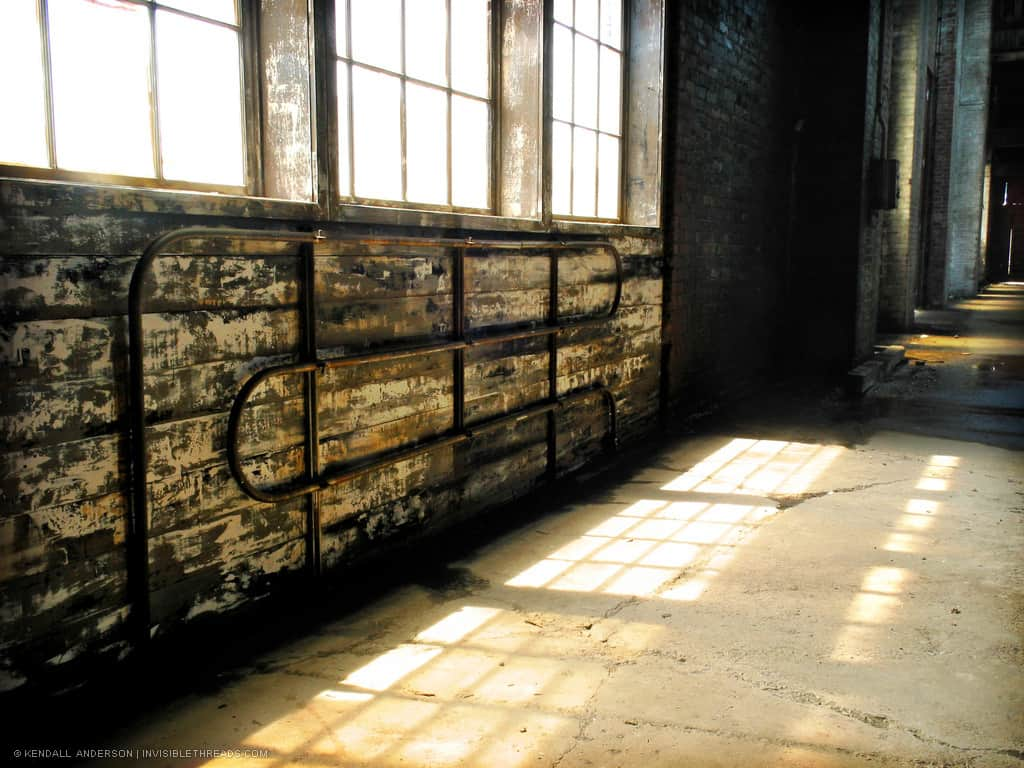 Light patterns from small square windows on dirt floor of empty industrial warehouse