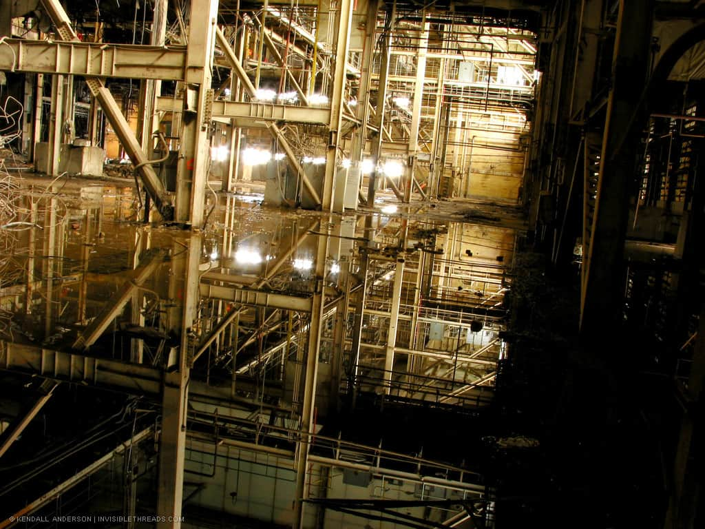 The ground floor interior of a large industrial power station is flooded with water. The water shows the reflection of the steel columns and beams inside.