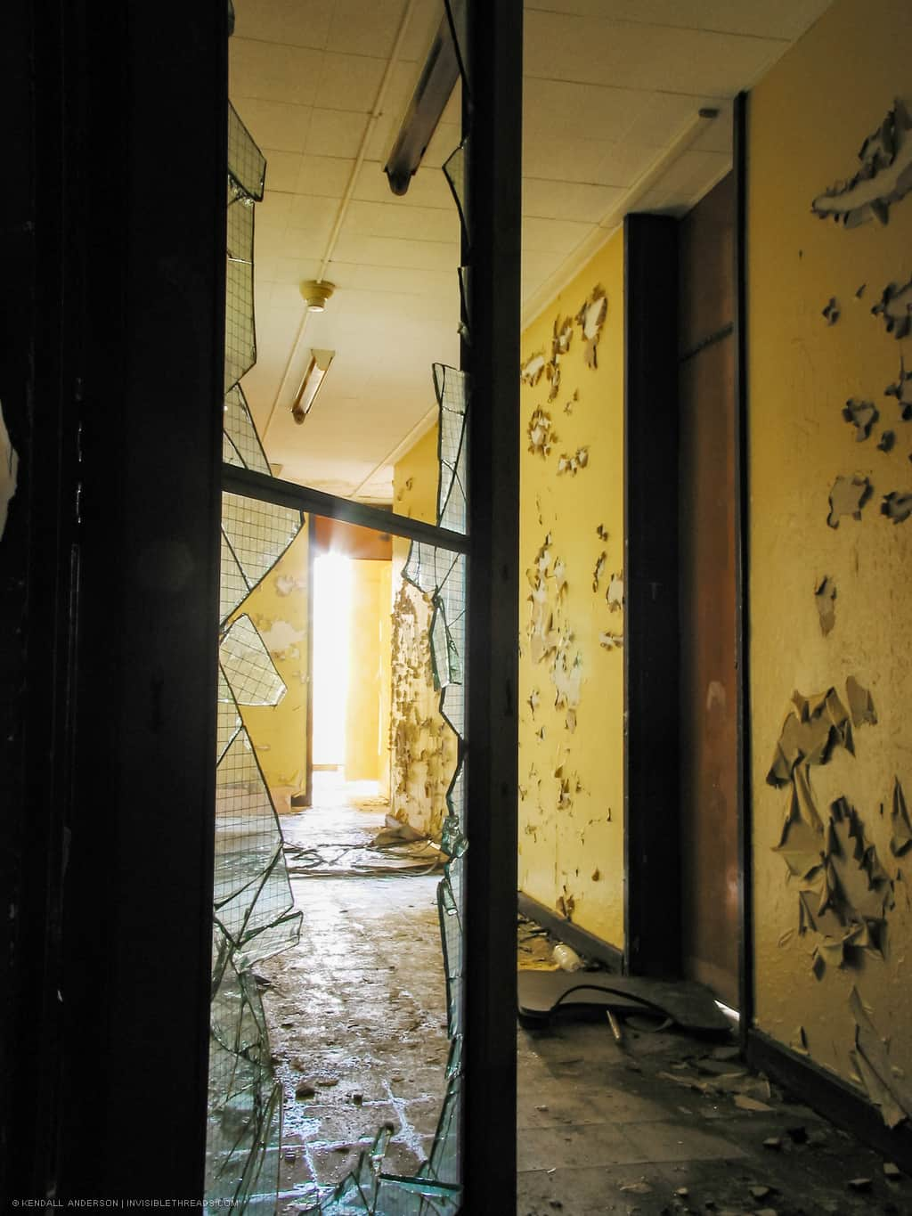 The interior of a school hallway is seen through a broken glass window in a door frame. The yellow walls are covered in peeling paint.