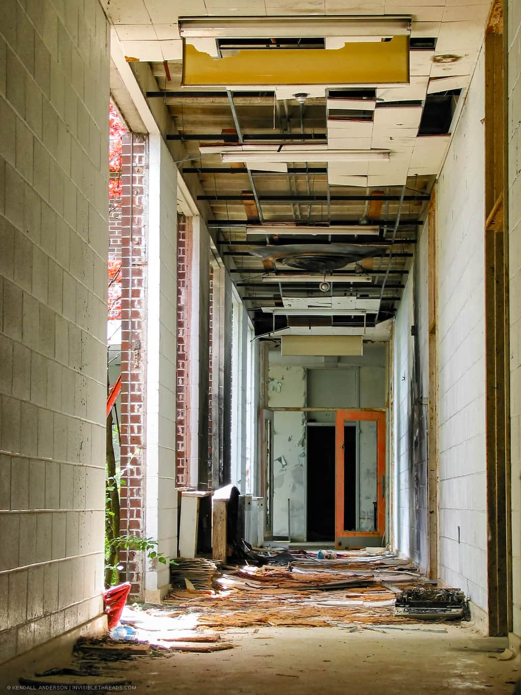 A long hallway filled with debris is brightly lit. All windows to an interior courtyard are broken, and the exit doors are missing all their glass.