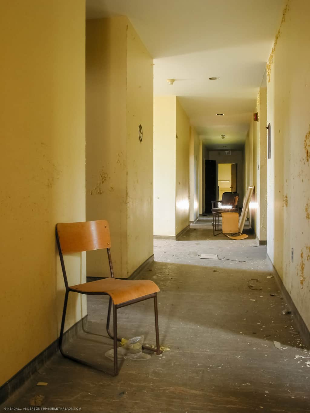 A chair is on the floor in a long yellow hallway, with additional chairs piled in the distance. The floor has debris on it and the paint on the walls is just beginning to show signs of water damage and peeling.