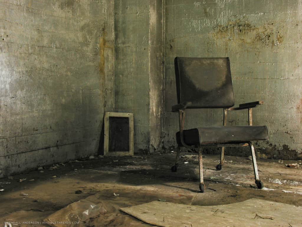 A grey office chair sits in the corner of an empty room. The surrounding concrete walls are dirty and grimy.