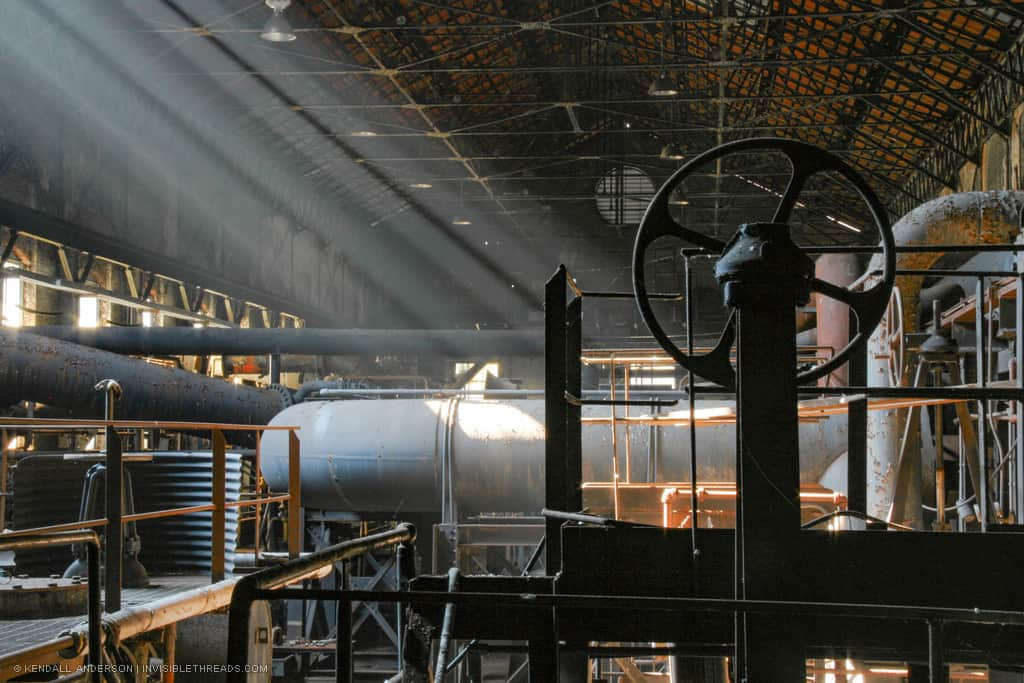 Shafts of light shine into the interior of a dark industrial building. The light reveals large metal pipes and railings densely packed into the building. The silhouette of a large valve wheel is in the foreground.