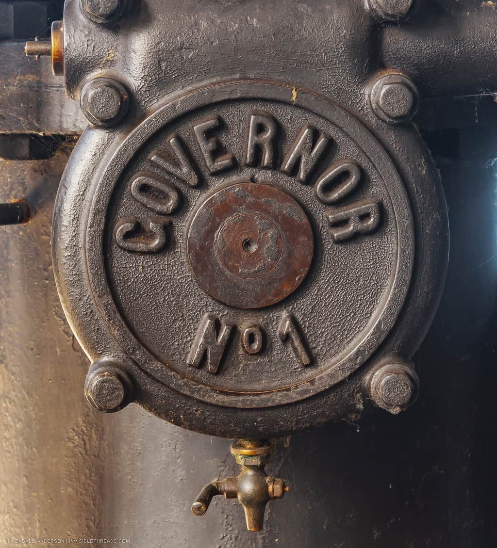 A textured steel disc has a small spout on the bottom. The steel disc has the words 'Governor No 1' embossed on it.