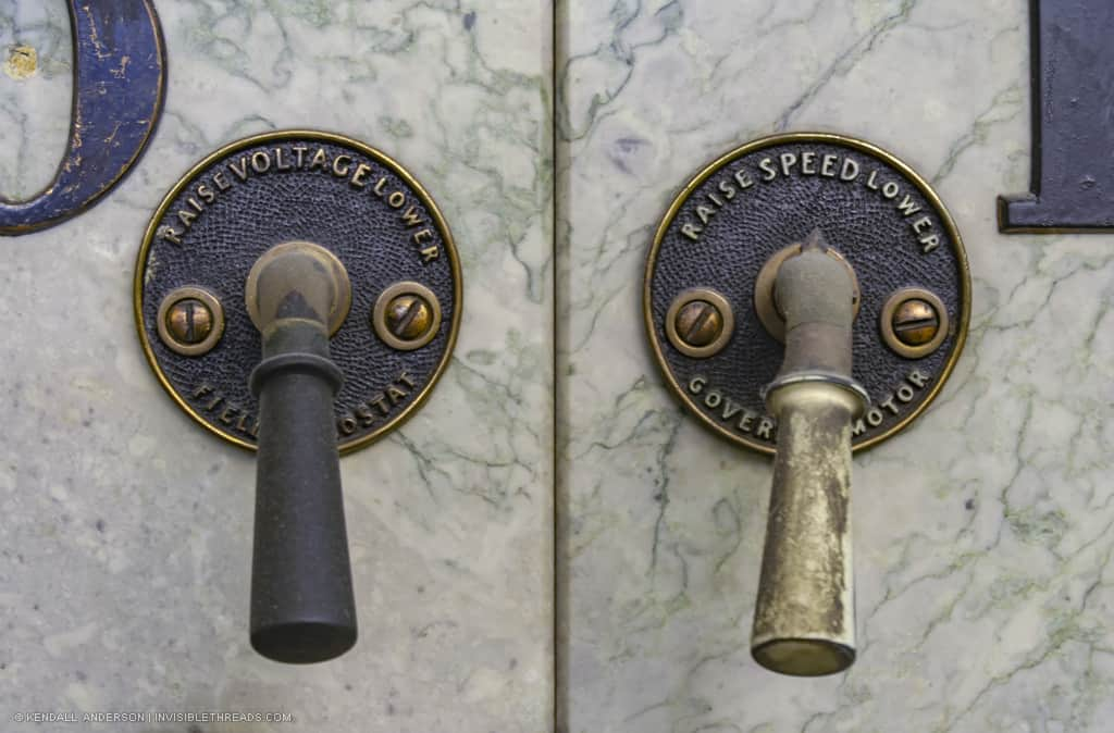 Two handles are mounted on a marble panel. The handle on the left is labelled 'Raise/Lower Voltage' and the handle on the right is labelled 'Raise/Lower Speed'.