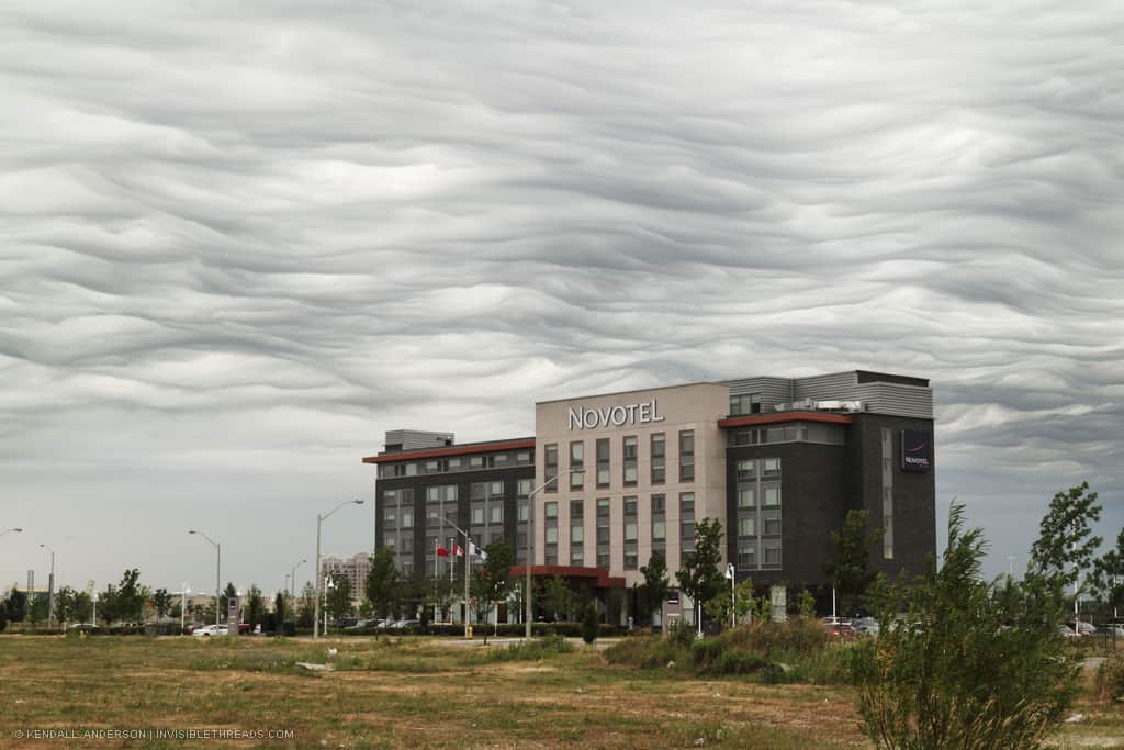 A 6-storey hotel building in the landscape, with wavy smoky cloud patterns in the sky beyond.
