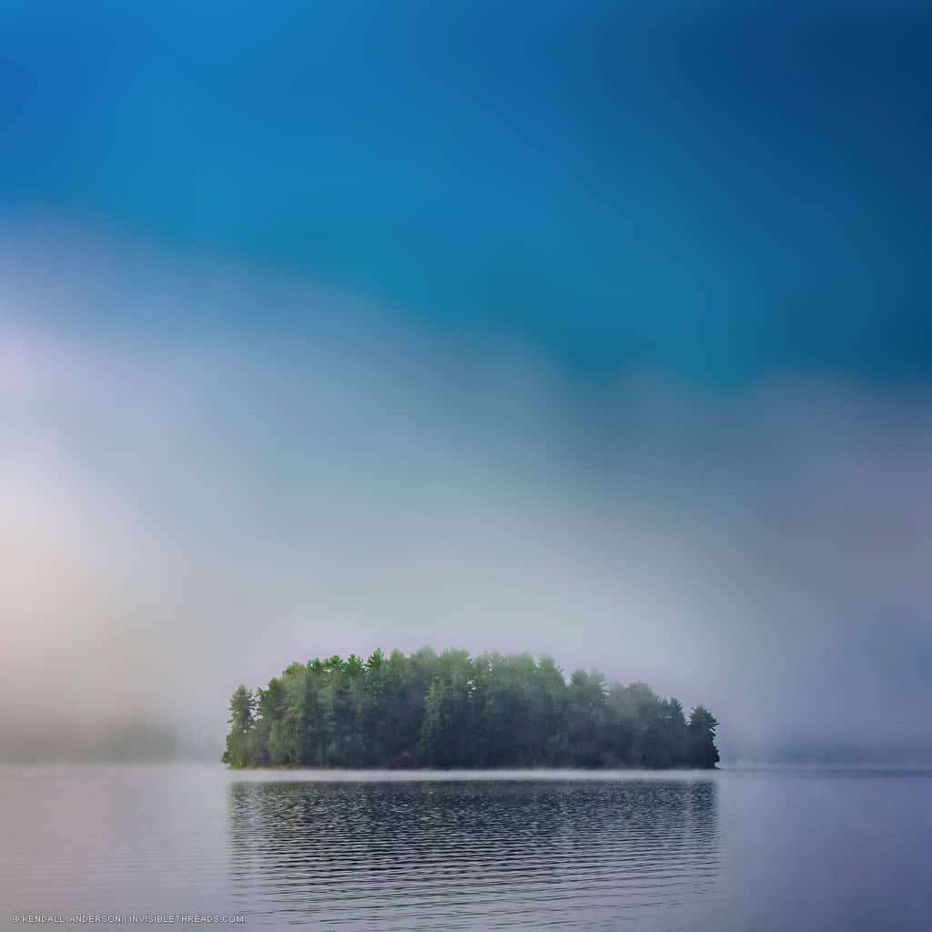 A single island covered with trees is surrounded by fog and mist on the lake water. The sky is also smooth with fog. The reflection of the island and trees is in the water in front of the island.