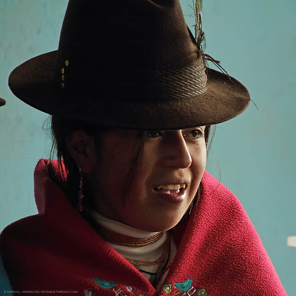 Portrait of a young indigenous girl, smiling and wearing traditional clothes: a bright red shawl and a brown fedora hat.