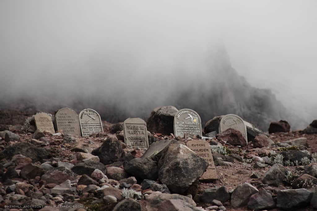 A group of 7 tombstones are set in the rocky mountain hillside, with thick fog and mist behind, obscuring Mount Chimborazo behind in the distance.